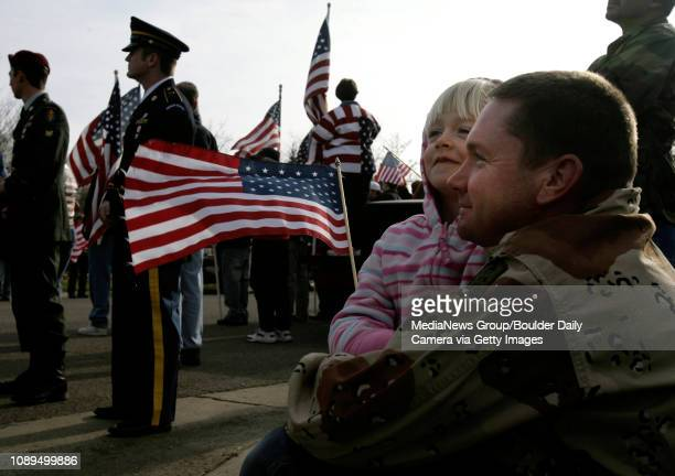Jeremy Berggren of Longmont and his daughter Rachel wait for a horsedrawn caisson carrying the body of Hospitalman Third Class Christopher A Anderson...