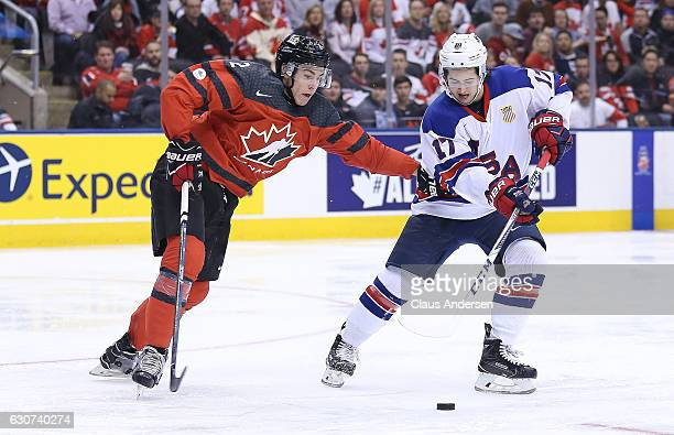 Jeremy Bracco of Team USA skates to avoid Jake Bean of Team Canada during a preliminary round game in the 2017 IIHF World Junior Hockey Championship...