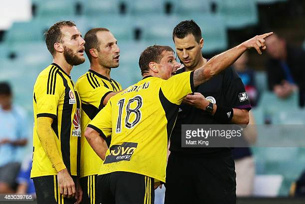 Jeremy Brockie Andrew Durante and Ben Sigmund of the Phoenix point to the reply after the referee awarded a penalty kick to Sydney FC which led to...