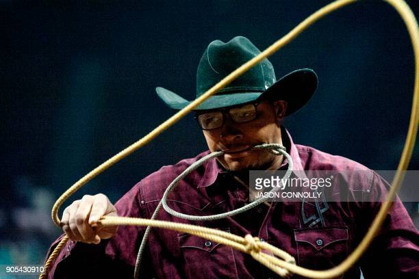 Jeremy Burkhalter prepares his lasso before riding out of the chutes during the Men's Calf Roping competition during the MLK Jr African American...
