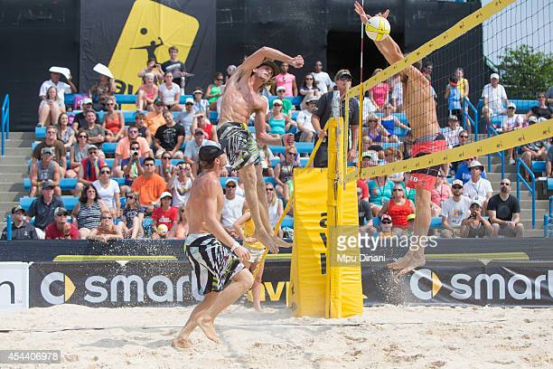 Jeremy Casebeer spikes the ball against Theo Brunner as Casey Jennings looks on at the 2014 AVP Cincinnati Open on August 30 2014 at the Lindner...