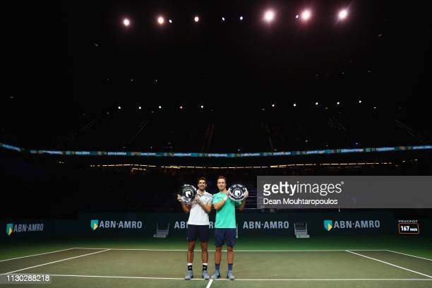 Jeremy Chardy of France and Henri Kontinen of Finland celebrate victory with the trophy against Jean-Julien Rojer of the Netherlands and Horia Tecau...