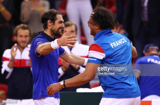 Jeremy Chardy of France celebrates with Yannick Noah the France captain following his victory during the singles match against Daniel Evans of Great...