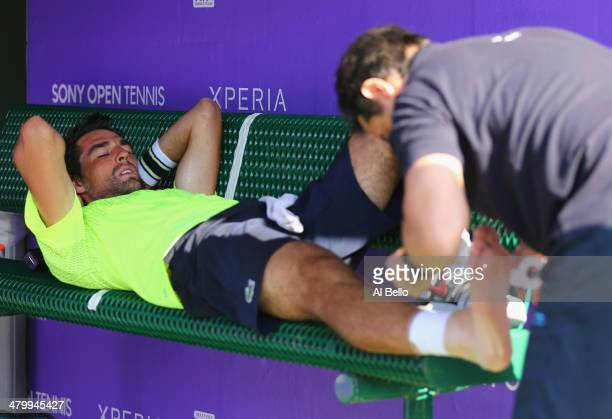 Jeremy Chardy of France has his ankle taped after falling during his match against Novak Djokovic of Serbia on day 5 of the Sony Open at Crandon Park...