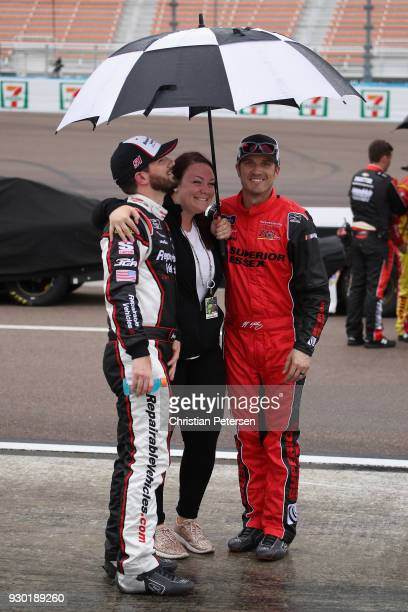 Jeremy Clements driver of the RepairableVehiclescom Chevrolet and JJ Yeley driver of the Superior Essex Chevrolet stands on the grid during ared flag...