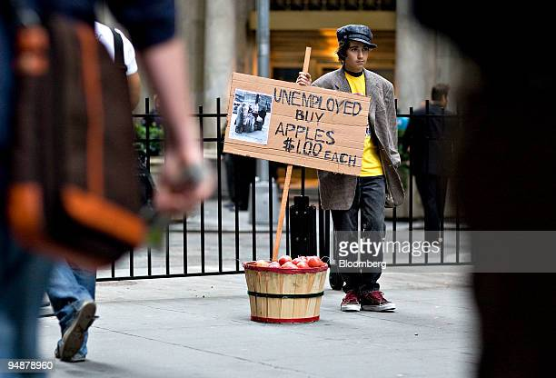 Jeremy Conway holds a sign reading Unemployed Buy Apples $100 Each next to a bucket of apples outside the New York Stock Exchange in New York US on...