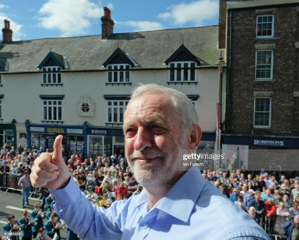 Jeremy Corbyn leader of the Labour Party gives a thumbs up as he stands on the balcony of the County Hotel as colliery bands pass below during the 133rd Durham Miners Gala on July 8, 2017 in Durham, England. Over two decades after the last pit closed in the Durham coalfield the Miners Gala or Big Meeting as it is known locally remains as popular as ever with over 200,000 people expected to attend this year. The gala forms part of the culture and heritage of the area and represents the communal values of the North East of England. The gala sees traditional colliery brass bands march through the city ahead of their respective pit banners and pausing to play outside the County Hotel building where union leaders, invited guests and dignitaries gather before then continuing to the racecourse area for a day of entertainment and speeches. Beginning in 1871 the gala is the biggest trade union event in Europe.