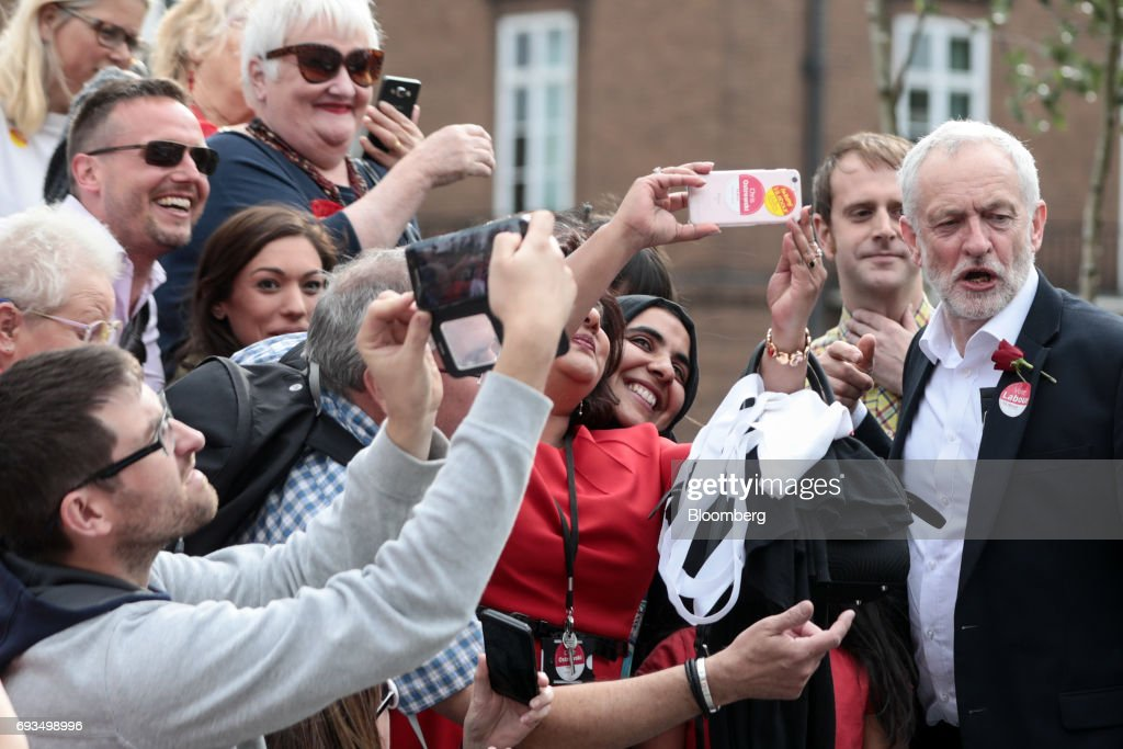 Jeremy Corbyn, leader of the U.K. opposition Labour Party, right, poses for selfie photographs with attendees during a general-election campaign rally in Watford, U.K., on Wednesday, June 7, 2017. The prime minister Theresa May and Corbyn, set out on whistle-stop tours of the country ahead of Thursday's vote, with polls all showing May's Conservatives ahead but disagreeing about whether the race is close.r. Photographer: Simon Dawson/Bloomberg via Getty Images