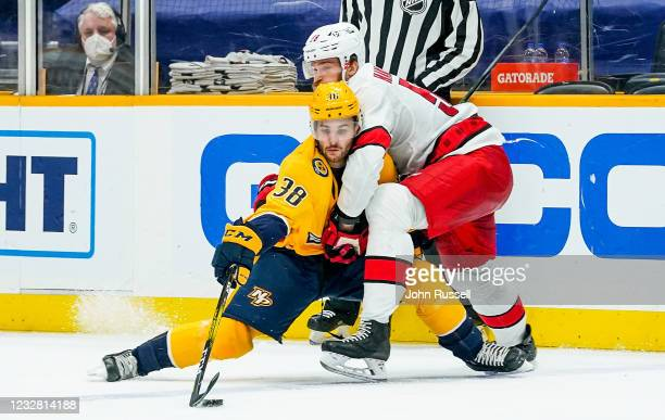 Jeremy Davies of the Nashville Predators battles for the puck against Jani Hakanpaa of the Carolina Hurricanes during the second period at...