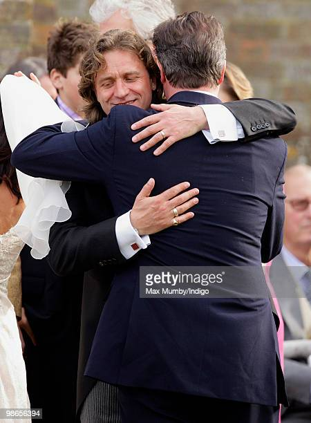 Jeremy Fawcus embraces his new brotherinlaw Conservative Party Leader David Cameron following his wedding to David's sister Clare at St Barnabus...