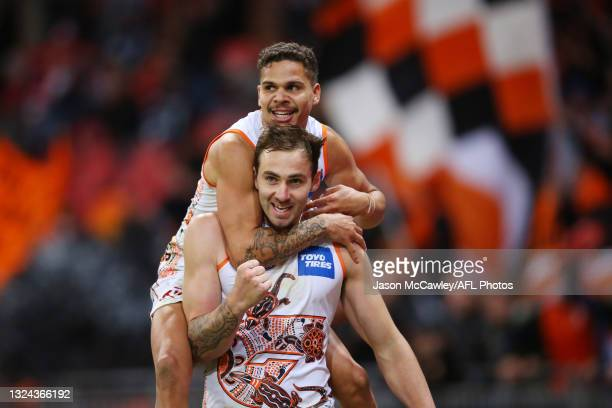 Jeremy Finlayson of the Giants celebrates kicking a goal with Bobby Hill of the Giants during the round 14 AFL match between the Greater Western...
