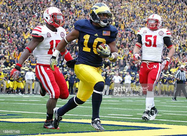 Jeremy Gallon of the Michigan Wolverines catches a first quarter pass in front of Alfonzo Dennard and Will Compton of the Nebraska Cornhuskers at...