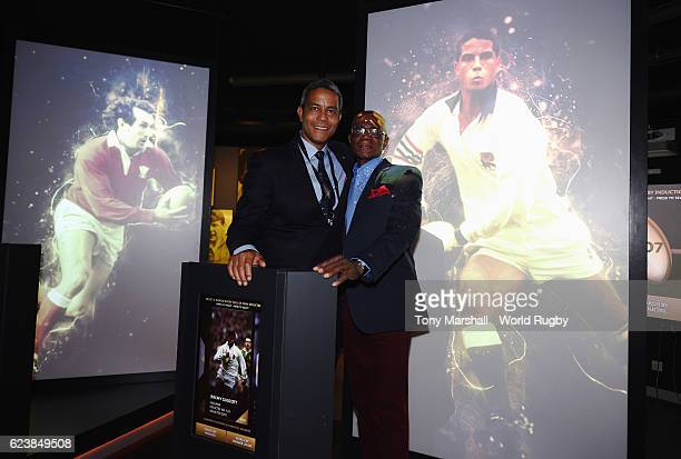 Jeremy Guscott and his father Henry pose with his profile in the World Rugby via Getty Images hall of Fame Exhibition during the World Rugby via...