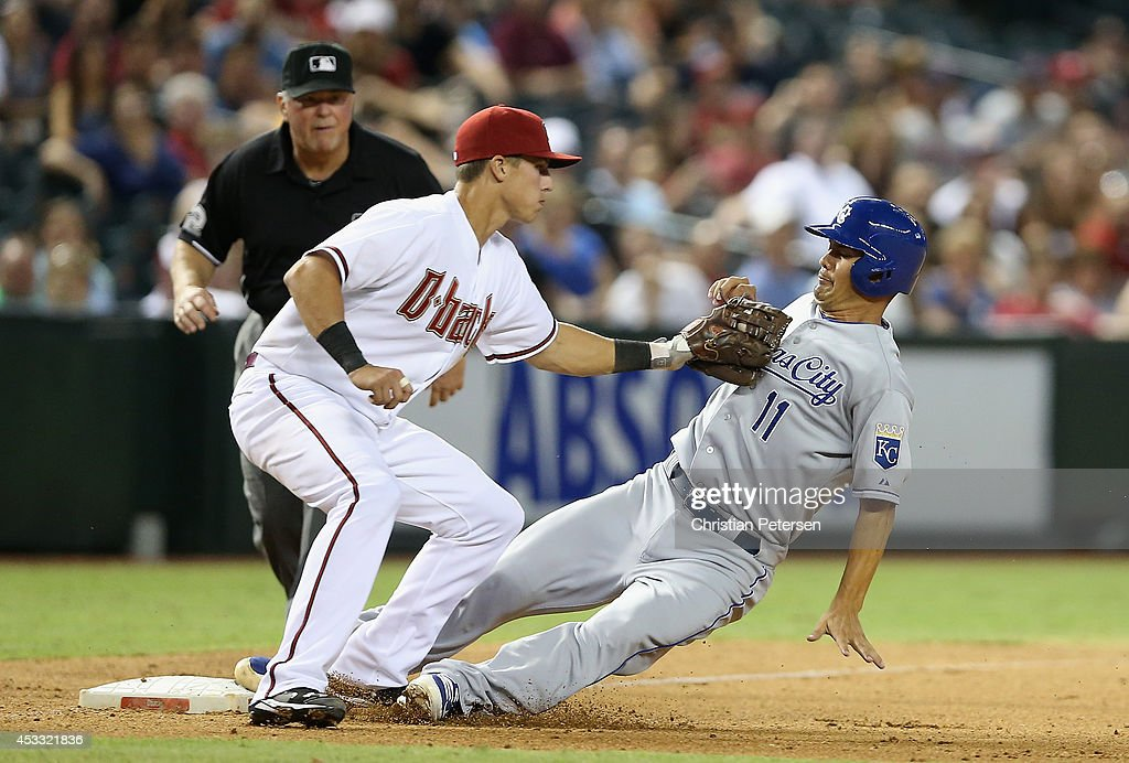 Jeremy Guthrie #11 of the Kansas City Royals safely slides into third base ahead of the tag from infielder Jake Lamb #19 of the Arizona Diamondbacks during the ninth inning of the MLB game at Chase Field on August 7, 2014 in Phoenix, Arizona.