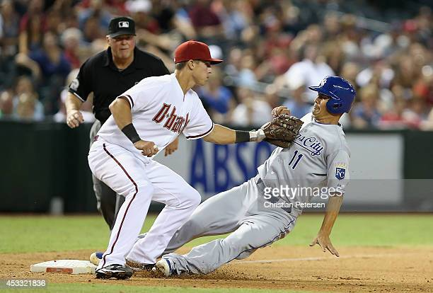 Jeremy Guthrie of the Kansas City Royals safely slides into third base ahead of the tag from infielder Jake Lamb of the Arizona Diamondbacks during...