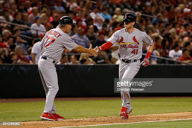 Jeremy Hazelbaker of the St Louis Cardinals is congratulated by third base coach Chris Maloney after hitting a tworun home run against the Arizona...