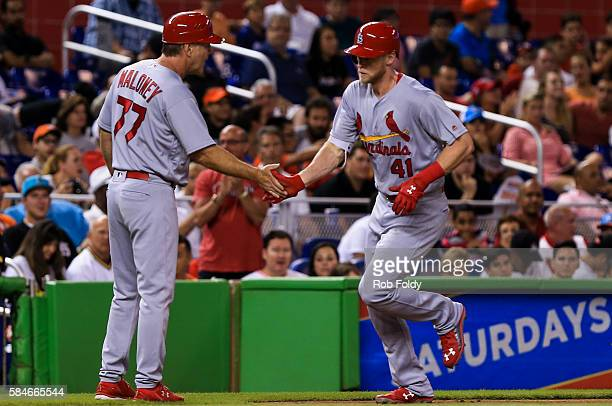 Jeremy Hazelbaker of the St Louis Cardinals slaps hands with third base coach Chris Maloney after hitting a two run home run during the second inning...