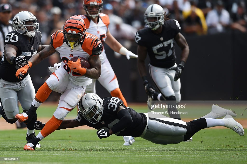 Jeremy Hill #32 of the Cincinnati Bengals is hit by Keith McGill #39 of the Oakland Raiders during the first half of their NFL game at O.co Coliseum on September 13, 2015 in Oakland, California.