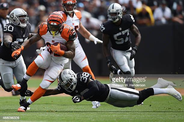 Jeremy Hill of the Cincinnati Bengals is hit by Keith McGill of the Oakland Raiders during the first half of their NFL game at Oco Coliseum on...