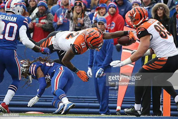 Jeremy Hill of the Cincinnati Bengals leaps over Stephon Gilmore of the Buffalo Bills for a touchdown during the first half at Ralph Wilson Stadium...