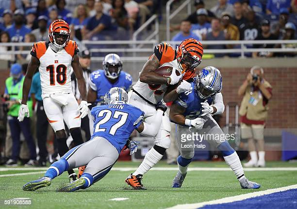 Jeremy Hill of the Cincinnati Bengals runs for a short gain as Glover Quin and Tavon Wilson of the Detroit Lions make the stop during the first...