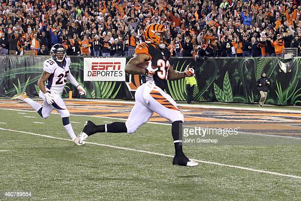 Jeremy Hill of the Cincinnati Bengals runs past Chris Harris Jr #25 of the Denver Broncos to score on an 85 yard run during the first quarter at Paul...