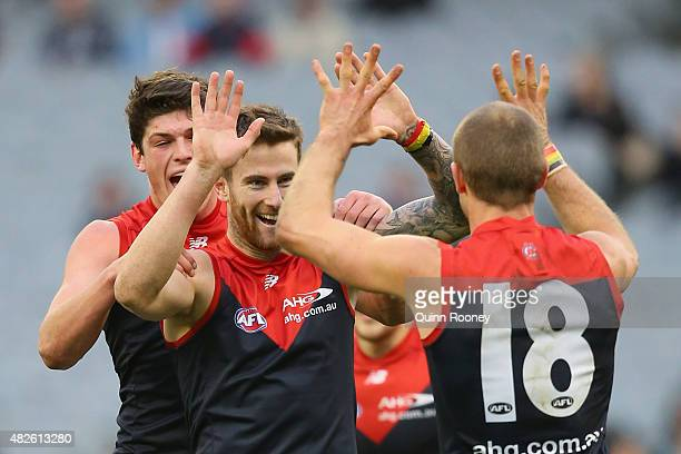 Jeremy Howe of the Demons is congratulated by Angus Brayshaw and Daniel Cross after kicking a goal during the round 18 AFL match between the...