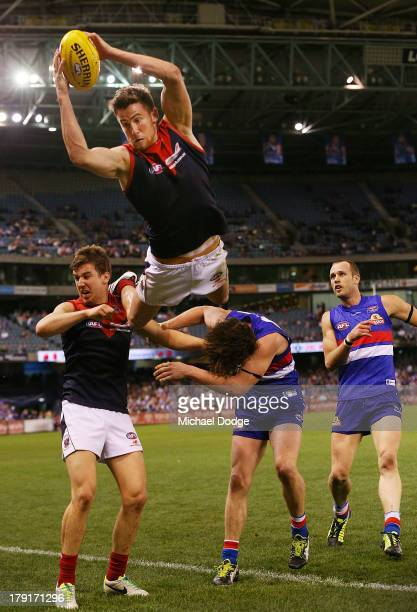 Jeremy Howe of the Demons marks the ball high over Jack Trengove and Liam Picken of the Bulldogs during the round 23 AFL match between the Western...