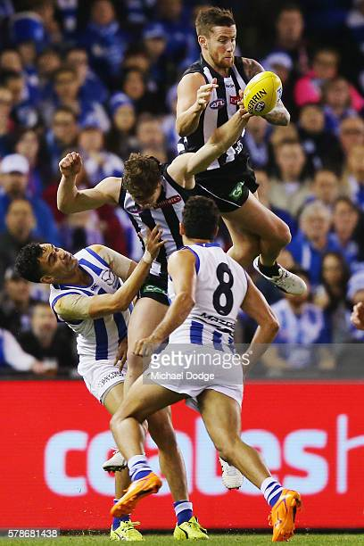 Jeremy Howe of the Magpies attempts a high mark over teammate Jack Crisp of the Magpies and Lindsay Thomas of the Kangaroos during the round 18 AFL...