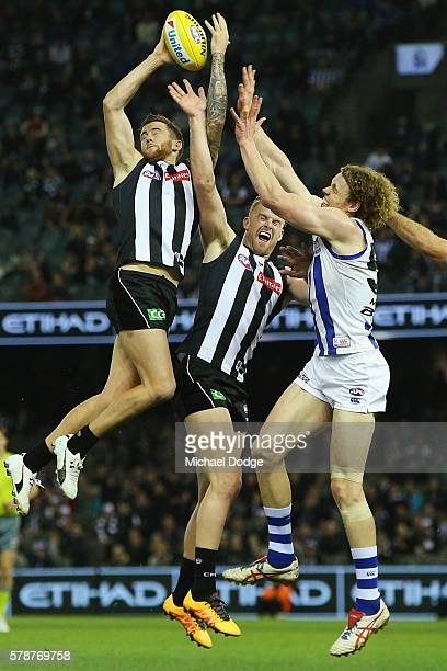 Jeremy Howe of the Magpies attempts a high mark over teammate Jordan de Goey of the Magpies and Ben Brown of the Kangaroos during the round 18 AFL...