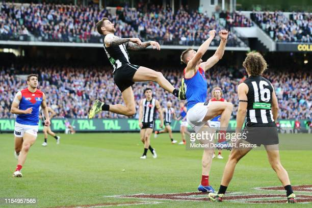 Jeremy Howe of the Magpies leaps into Tom McDonald of the Demons for an attempted mark but was penalised during the AFL Round 12 match between...
