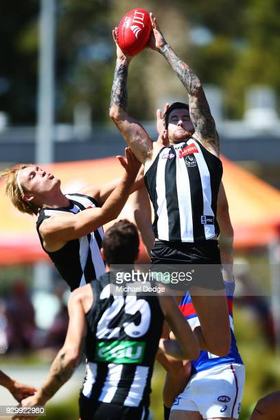 Jeremy Howe of the Magpies marks the ball next to Darcy Moore during the JLT Community Series AFL match between Collingwood Magpies and the Western...