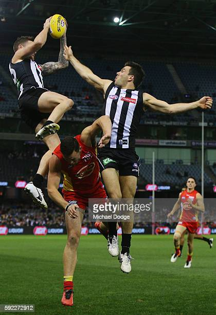 Jeremy Howe of the Magpies marks the ball over Steven May of the Suns during the round 22 AFL match between the Collingwood Magpies and the Gold...