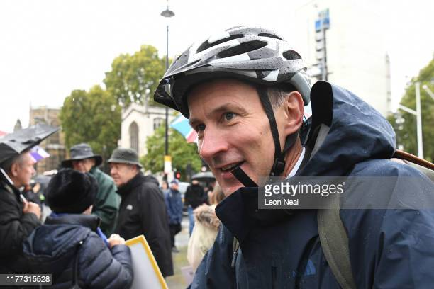 Jeremy Hunt MP arrives at carriage gate entrance for the Houses of Parliament in Westminster on his bicycle on October 21 2019 in London England...