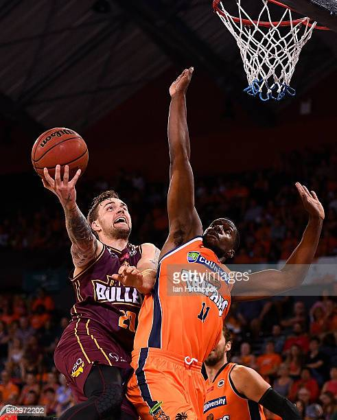 Jeremy Kendle of the Bullets attempts a lay up over Tony Mitchell of the Taipans during the round 17 NBL match between the Cairns Taipans and the...