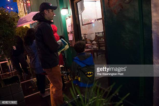 DECEMBER 6 Jeremy Koenig of Washington DC and his son Will wait outside Comet Ping Pong in Washington DC on Tuesday December 6 2016 The business...