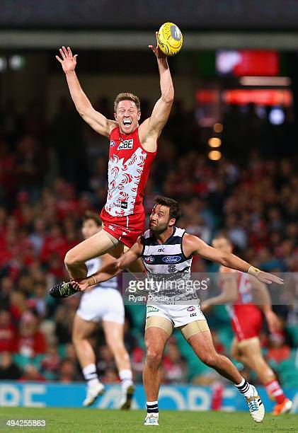 Jeremy Laidler of the Swans leaps over Jimmy Bartel of the Cats during the round 11 AFL match between the Sydney Swans and the Geelong Cats at the...