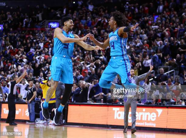 Jeremy Lamb of the Charlotte Hornets celebrates with Devonte Graham after sinking a buzzer beater to win an NBA game against the Toronto Raptors at...