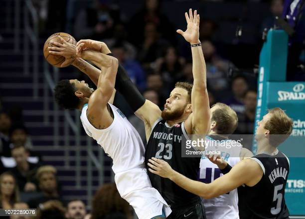 Jeremy Lamb of the Charlotte Hornets tries to shoot over Blake Griffin of the Detroit Pistons during their game at Spectrum Center on December 12...