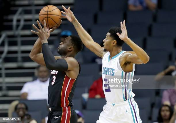Jeremy Lamb of the Charlotte Hornets tries to stop Dwyane Wade of the Miami Heat during their game at Spectrum Center on October 2 2018 in Charlotte...