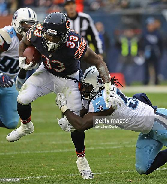 Jeremy Langford of the Chicago Bears gets tripped up by Sean Spence of the Tennessee Titans at Soldier Field on November 27 2016 in Chicago Illinois...
