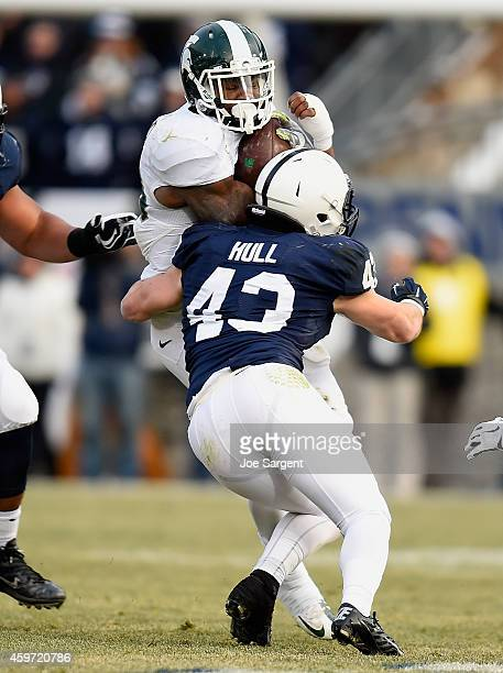 Jeremy Langford of the Michigan State Spartans gets wrapped up by Mike Hull of the Penn State Nittany Lions at Beaver Stadium on November 29, 2014 in...