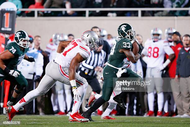 Jeremy Langford of the Michigan State Spartans runs for a 33-yard touchdown in the first quarter of the game against the Ohio State Buckeyes at...