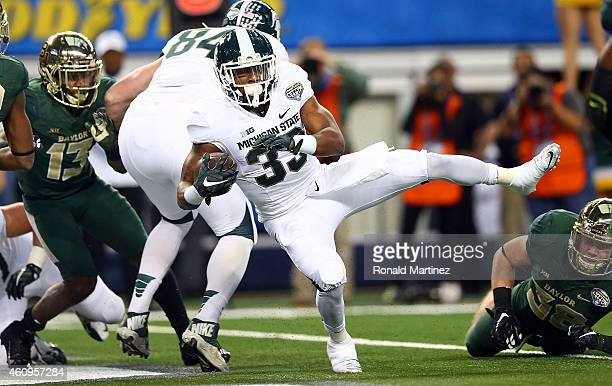 Jeremy Langford of the Michigan State Spartans runs for a touchdown against the Baylor Bears during the first half of the Goodyear Cotton Bowl...
