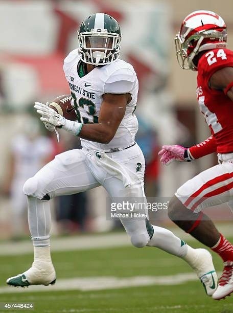 Jeremy Langford of the Michigan State Spartans runs the ball as Tim Bennett of the Indiana Hoosiers pursues at Memorial Stadium on October 18, 2014...