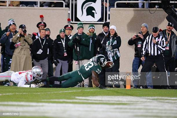 Jeremy Langford of the Michigan State Spartans tackled by Tyvis Powell of the Ohio State Buckeyes against the Ohio State Buckeyes at Spartan Stadium...