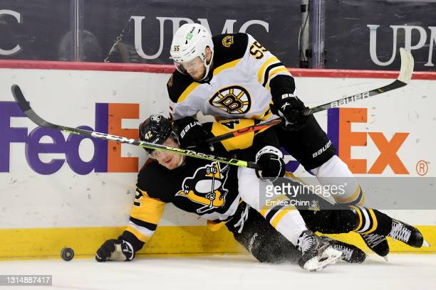 Jeremy Lauzon of the Boston Bruins and Kasperi Kapanen of the Pittsburgh Penguins battle for the puck in the second period during their game at PPG...