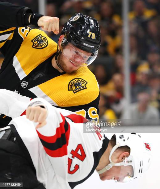 Jeremy Lauzon of the Boston Bruins fights Nathan Bastian of the New Jersey Devils during the second period of the preseason game between the New...
