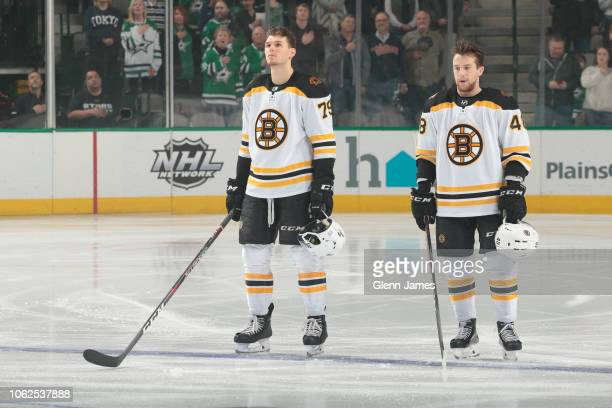 Jeremy Lauzon stands next to Matt Grzelcyk of the Boston Bruins before a game against the Dallas Stars at the American Airlines Center on November...