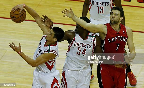 Jeremy Lin and Patrick Patterson of the Houston Rockets battle with Andres Bargnan of the Toronto Raptors for the ball at the Toyota Center on...